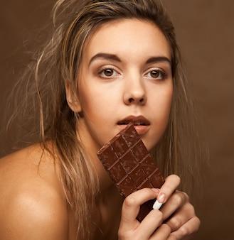 Fröhliche junge frau, die schokolade isst