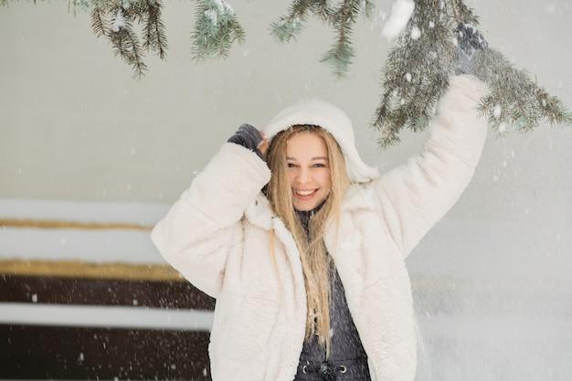 Fröhliche junge frau, die spaß mit schnee im park hat