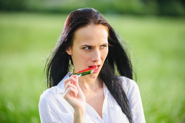 Fröhliche junge frau, die süßigkeiten in form von wassermelonenscheiben nahe ihrem gesicht hält. mädchen, das in der natur mit lutschern ruht.