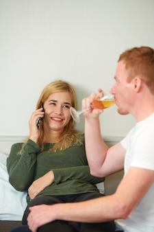 Fröhliche junge frau, die telefoniert, um pizza für ein romantisches abendessen zu hause zu bestellen?