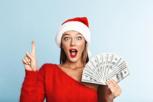 Fröhliche junge frau, die weihnachtsmannhut trägt, geldbanknoten zeigt, finger nach oben zeigt