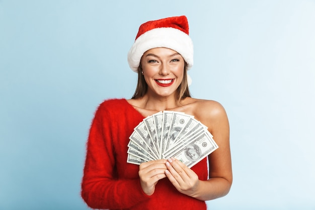 Fröhliche junge frau, die weihnachtsmannhut trägt und geldbanknoten zeigt