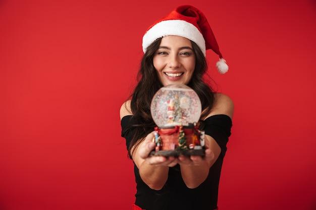 Fröhliche junge frau, die weihnachtsmütze trägt, die lokal über rot steht und schneekugel hält