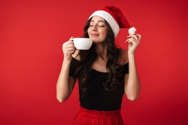Fröhliche junge frau, die weihnachtsmütze trägt, die lokal über rot steht und tasse heiße schokolade hält