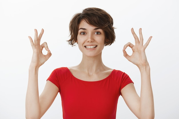 Fröhliche junge frau garantieren perfekte qualität, empfehlen produkt, zeigt gute geste