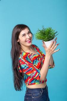 Fröhliche junge frau hält einen topf mit einer pflanze, die gegen eine blaue wand aufwirft. konzept der garten- und innenausstattung.