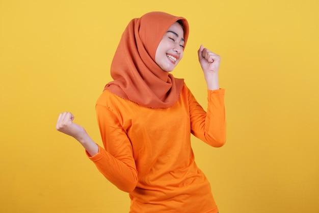 Fröhliche junge frau hat einen positiven ausdruck, hat ein überglückliches aussehen, ist in hochstimmung und trägt lässig hijab