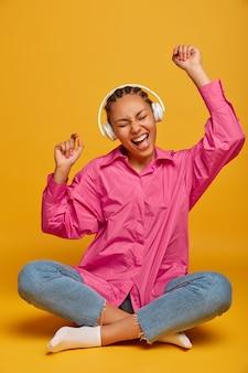 Fröhliche junge frau hört audio-track in kopfhörern, hebt die arme, sitzt in lotus-pose an der gelben wand, bewegt sich im rhythmus der musik, voller energie, fühlt sich glücklich und entspannt. menschen, freizeit