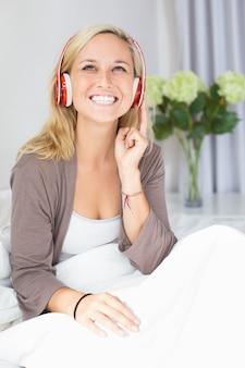 Fröhliche junge frau hört musik oder hörbuch