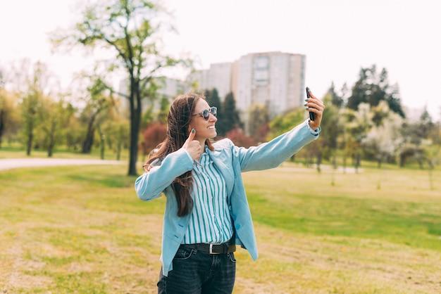 Fröhliche junge frau im blauen anzug, die im park spazieren geht und mit dem smartphone selfie macht und im freien daumen zeigt