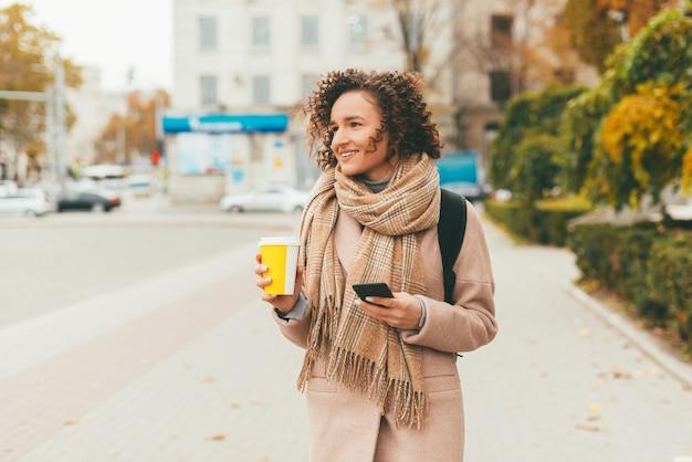 Fröhliche junge frau im freien während des herbstspaziergangs auf den straßen der stadt und beim trinken einer tasse kaffee