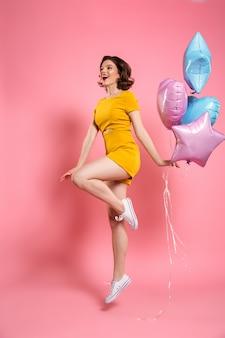 Fröhliche junge frau im gelben kleid, das ballons hält