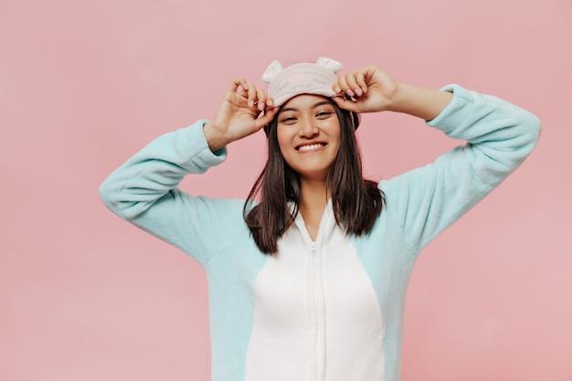 Fröhliche junge frau im mintfarbenen pyjama lächelt aufrichtig, schaut nach vorne und setzt eine schlafmaske auf