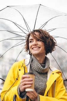 Fröhliche junge frau im regenmantel gekleidet