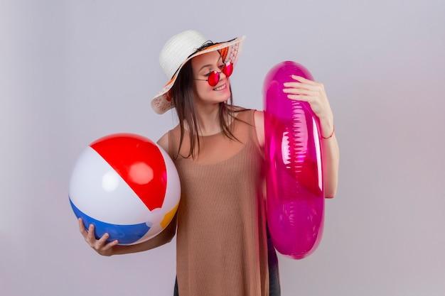 Fröhliche junge frau im sommerhut, die rote sonnenbrille hält, die aufblasbaren ball und ring lächelnd aufblasenden ring stehend betrachtet