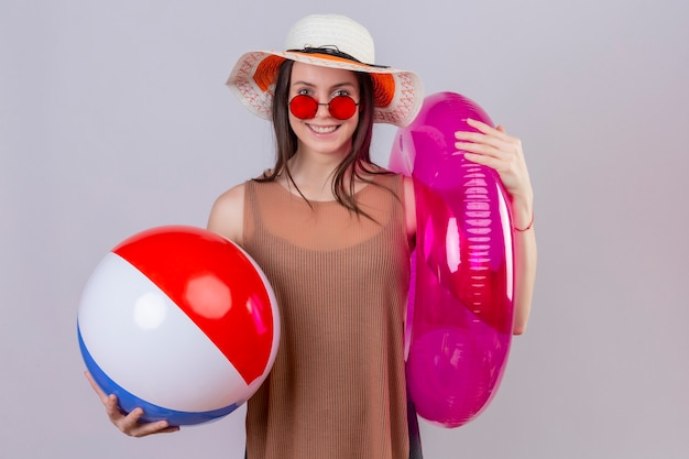 Fröhliche junge frau im sommerhut, die rote sonnenbrille hält, die aufblasbaren ball und ring lächelnd stehend hält