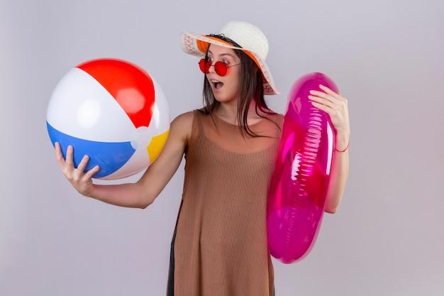 Fröhliche junge frau im sommerhut, die rote sonnenbrille hält, die aufblasbaren ring und ball hält, die es überrascht und glücklich stehend betrachten