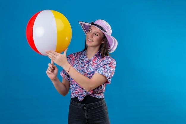 Fröhliche junge frau im sommerhut hält aufblasbaren ball lächelnd mit glücklichem gesicht, das über blauem raum steht