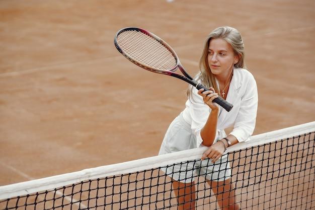 Fröhliche junge frau im t-shirt. frau, die tennisschläger und ball hält.