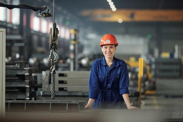 Fröhliche junge frau in arbeitskleidung und schutzhelm, die sie beim arbeiten in der modernen industrieanlage betrachten