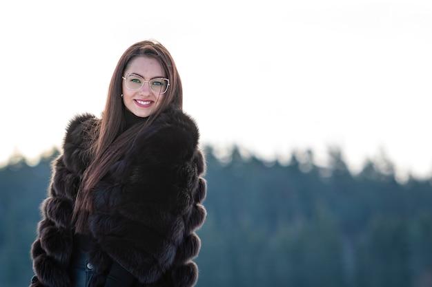 Fröhliche junge frau in einem warmen pelzmantel, der einen wintertag im verschneiten wald genießt