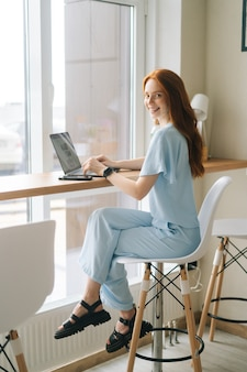 Fröhliche junge frau in freizeitkleidung, die auf laptop-computer am tisch am fenster im café sitzt und in die kamera schaut. hübsche rothaarige kaukasische dame, die fern arbeitet oder studiert