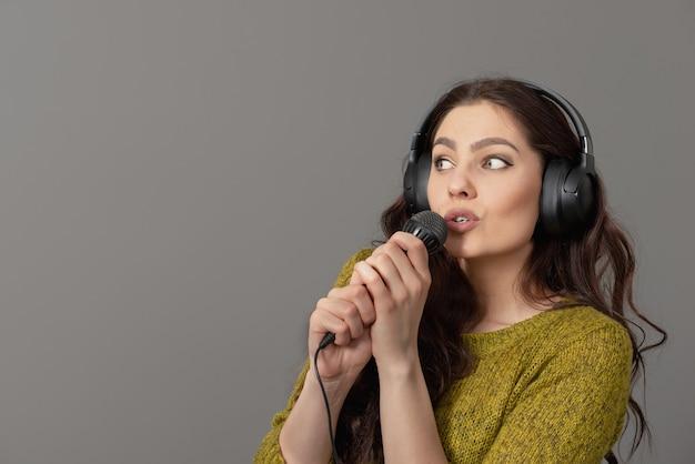 Fröhliche junge frau in freizeitkleidung mit kopfhörern singen lied im mikrofon, verspotten kopierraum