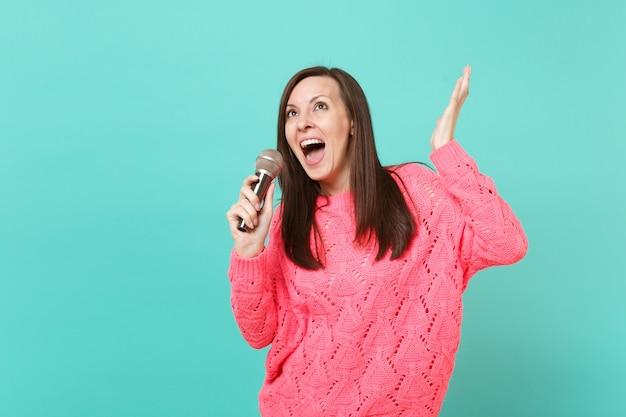 Fröhliche junge frau in gestricktem rosa pullover tanzt, hände ausbreitend, singen lied im mikrofon einzeln auf blauem wandhintergrund, studioporträt. menschen lifestyle-konzept. kopieren sie platz.