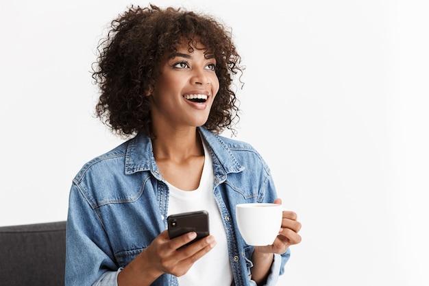 Fröhliche junge frau in legerer denim-kleidung sitzt auf einem stuhl isoliert über weißer wand, hält eine tasse kaffee und benutzt handy