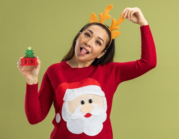 Fröhliche junge frau in rotem weihnachtspullover mit lustiger felge mit hirschhörnern, die spielzeugwürfel mit datum fünfundzwanzig zeigt, die die zunge über grüner wand ragen