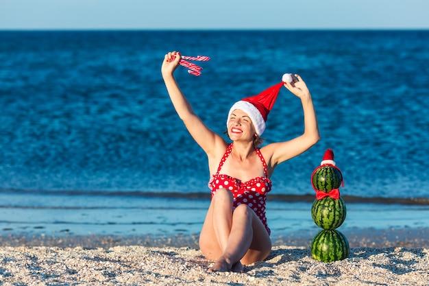 Fröhliche junge frau in sankt-hut hält weihnachtszuckerstangen und wassermelonen-schneemann steht in der nähe.
