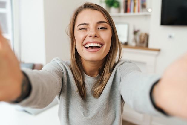 Fröhliche junge frau lacht und zwinkert beim selfie im wohnzimmer