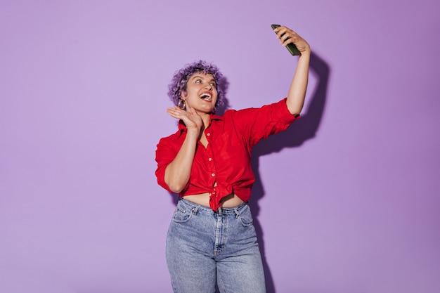 Fröhliche junge frau lächelt aufrichtig und posiert auf flieder. nette schöne frau in jeans nimmt selfie.
