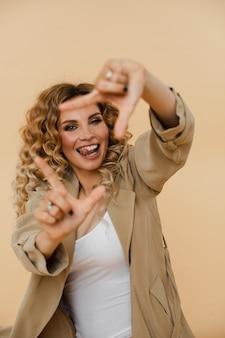 Fröhliche junge frau lächelt und macht einen rahmen mit ihren fingern. modekonzept