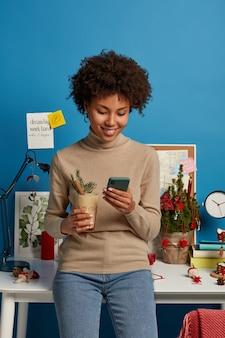 Fröhliche junge frau mit afro-haar überprüft newsfeed auf dem smartphone, zufrieden, nachrichten und kommentare der follower unter ihrem beitrag zu lesen, trinkt eierlikör-cocktail steht in der nähe des arbeitsplatzes konzentriert auf dem bildschirm