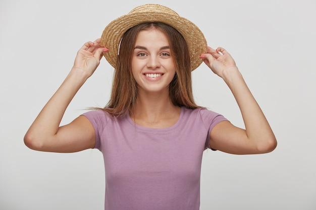 Fröhliche junge frau mit angenehmem lächeln, hat lange braune haare, hält in händen strohhut