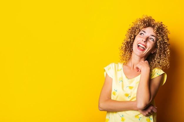 Fröhliche junge frau mit den lockigen haaren, die auf einem hellen gelben hintergrund lacht