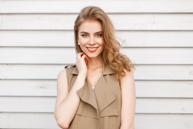 Fröhliche junge frau mit einem niedlichen lächeln mit natürlichem make-up mit blauen augen in einer eleganten sommerbeigeweste nahe einer weißen holzwand. freudiges positives mädchen
