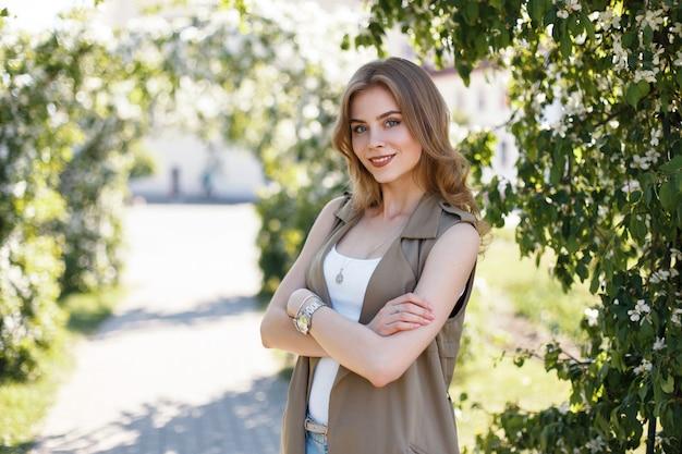 Fröhliche junge frau mit einem schönen lächeln mit lockigem blondem haar in einer stilvollen sommerweste in einem weißen t-shirt, das aufwirft