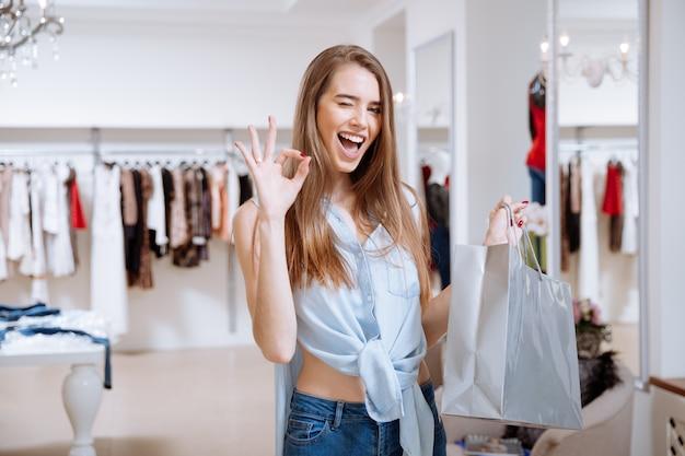 Fröhliche junge frau mit einkaufstasche zwinkert und zeigt ok zeichen im bekleidungsgeschäft