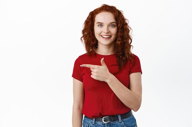 Fröhliche junge frau mit ingwer lockigen haaren, die mit dem finger nach links zeigt und glücklich lächelt, einladende promo-angebote an der weißen wand