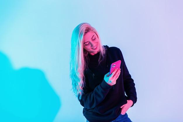 Fröhliche junge frau mit lächeln in schwarzem hoodie und blauer jeans mit smartphone-eingabenachricht im studio auf neonrosa hellem hintergrund
