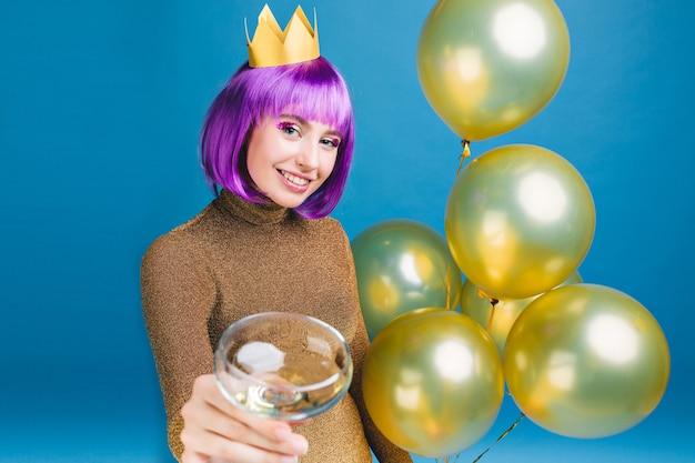 Fröhliche junge frau mit lila haarschnitt, die neujahrsparty mit goldenen luftballons und champagner feiert. luxuskleid, krone auf dem kopf, geburtstag, alkoholcocktail trinkend.