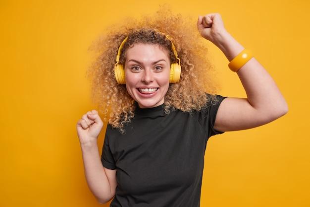 Fröhliche junge frau mit natürlichem lockigem haar hebt arme tanzt unbeschwert genießt lieblingsmusik in kopfhörern hat spaß gekleidet in schwarzem t-shirt isoliert über gelber wand. unterhaltungskonzept