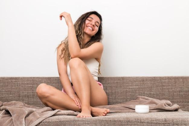 Fröhliche junge frau mit perfekter körperhaut nach feuchtigkeitsspendendem körper, die auf sofa zu hause sitzt