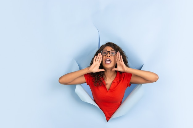 Fröhliche junge frau posiert in einem zerrissenen blauen papierloch, emotional und ausdrucksstark