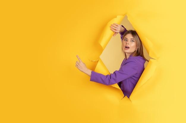 Fröhliche junge frau posiert in einem zerrissenen gelben papierloch, emotional und ausdrucksstark