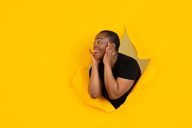 Fröhliche junge frau posiert in zerrissener gelber papierlochwand emotional und ausdrucksstark mit lautsprecher