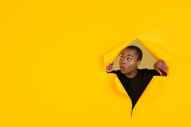 Fröhliche junge frau posiert in zerrissener gelber papierlochwand emotional und ausdrucksstark