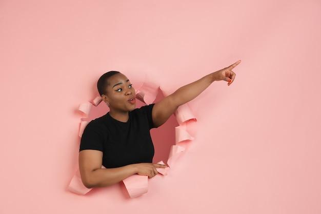 Fröhliche junge frau posiert in zerrissener korallenpapierlochwand emotional und ausdrucksstark Kostenlose Fotos
